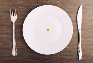 diet concept. one pea on an empty white plate with knife and fork